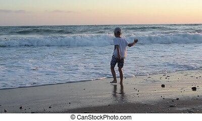 Boy jumping on a sandy beach by the sea with waves on a sunset background