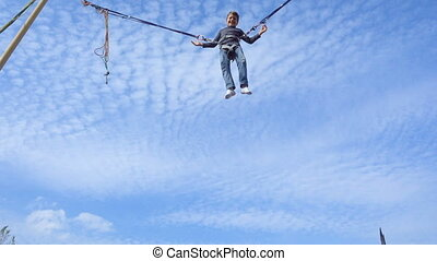 Boy jumping on bungee trampoline - Young boy jumping on...