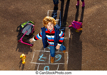 Boy jumping on hopscotch game - Nice blond boy jumping over...