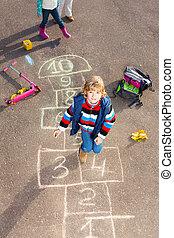 Boy jumping on hopscotch - Boy jumping on the hopscotch game...