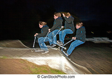 boy jumping over a ramp by night