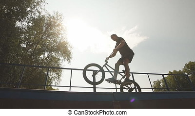 boy jumping with BMX Bike at skate park - Table top in...