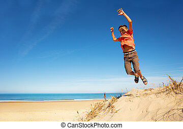 Boy jumps from sand dune on a beach rising hands