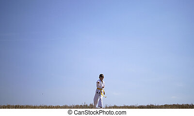 Boy Karate Training In The Field Against The Sky