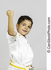 Boy Karate Uppercut - A young boy punching up dressed in a...