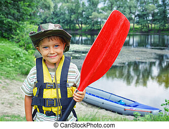 boy kayaking - Portrait of happy young boy holding paddle...