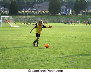 Boy kicking a ball on the field.