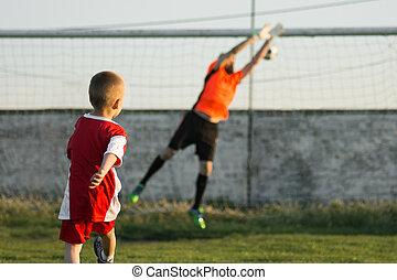 boy kicking a goal