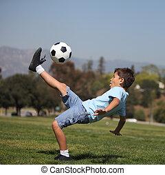 Boy kicking soccer ball - A young boy performs a soccer...