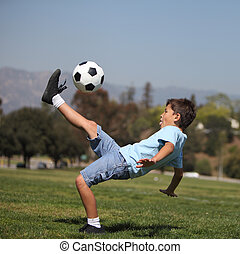 Boy kicking soccer ball - A young boy performs a soccer...