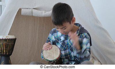 Boy kid playing on traditional african drums djembe on wigwam background indoors
