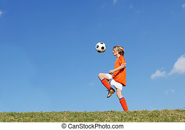 boy kid playing soccer kicking football.