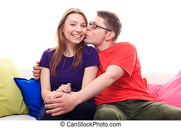 Boy kissing a girl on the sofa at home