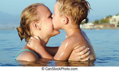 Boy kissing and embracing mother in sea