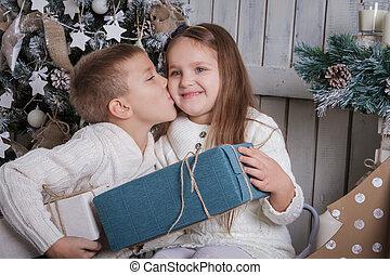 Boy kissing girl on cheek with Christmas gift