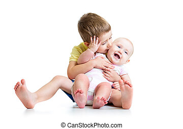 Boy kissing his little sister baby isolated on white