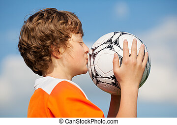 Boy Kissing Soccer Ball Against Sky - Side view of young boy...