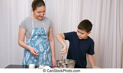 Boy kneading dough with a whisk under the supervision of a woman.