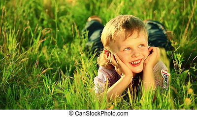 Boy laughing. Lying in the grass.