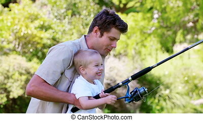 Boy laughing while fishing with his father in a park