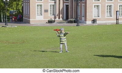 boy launches model airplane in park on June