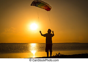Boy launching the rainbow kite at sunset