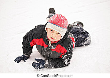 Boy laying down on snow