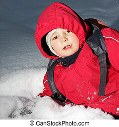 Boy laying in snow