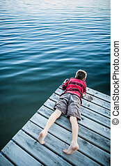 Boy laying on a dock looking at the water