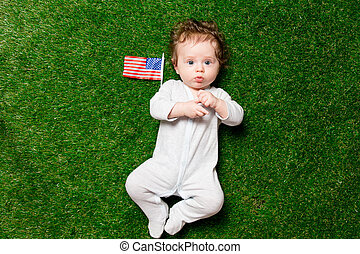 boy laying on grass with USA flag