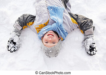 Boy Laying On Ground Making Snow Angel
