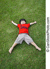 Boy laying on the green grass