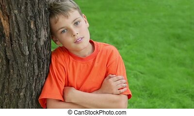 boy leans against tree and smile, closeup view at summer day