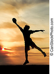 Boy leaping for the football at sunset.