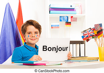 Boy learning French sitting at desk in classroom
