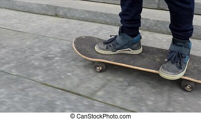 Boy learning hot to skate riding on the granite