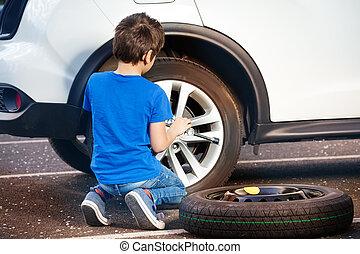 Boy learning how to change tyre using wheel brace - Back ...