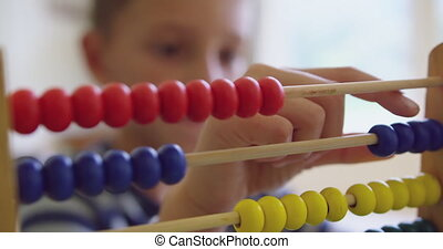 Close-up of Caucasian boy learning mathematics with abacus in a comfortable home 4k