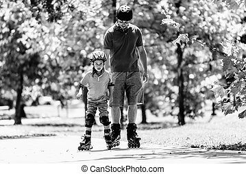 Boy learning roller skating - Father teching son roller...