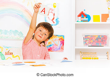 Boy learns to read showing letter card