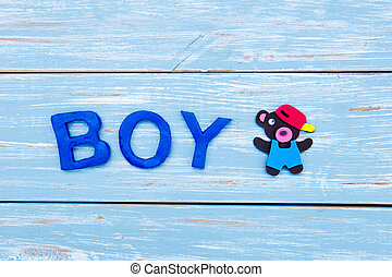Boy - letters with bear on blue wooden background