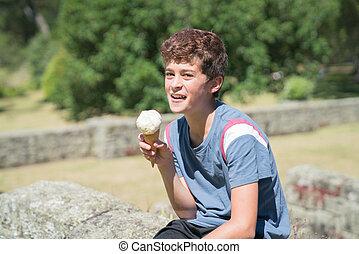 Boy licking ice cream outdoors.