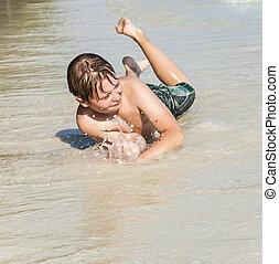 boy lies at the beach and enjoys rolling in the sand - boy...