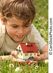 boy lies in grass with house model in hands