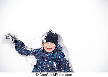 boy lies on north pole snow. kis happy and smiling.