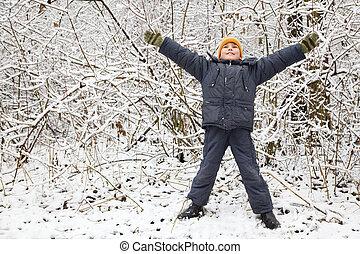 boy lifted hands upwards in wood in winter