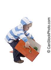 Boy lifting box - A three years old boy lifting a wooden...