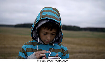 Boy listening to music from your phone, boy in a field on the mountain in the evening