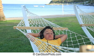 Boy listening to music in a hammock