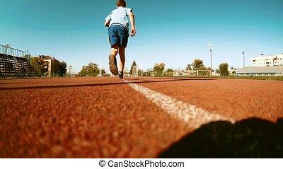 Boy little runner running on outdoor stadium race track....
